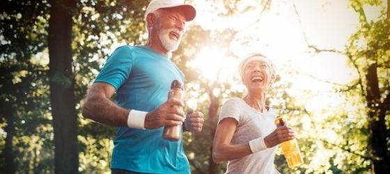 Running couple holding water bottles